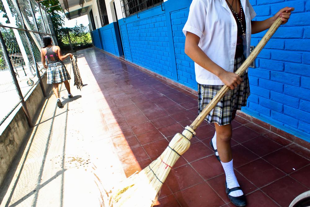 Al finalizar las clases, alumnas hacen la limpieza en los pasillos de la Escuela Santa Mónica, en La Coyotera, Quezaltepeque. Foto de Frederick Meza.