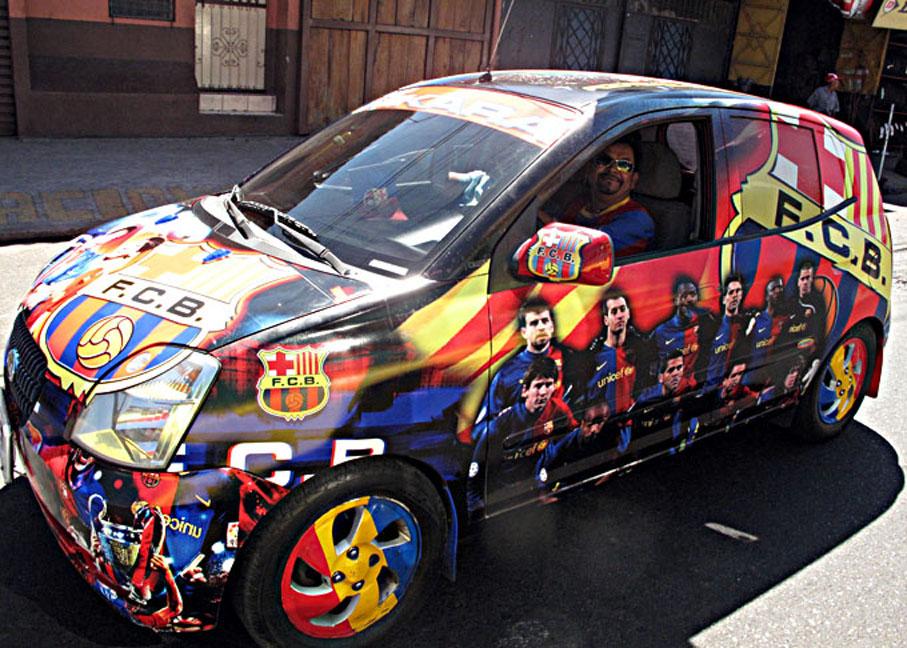 Un aficionado del Barcelona FC luce orgulloso el carro que ha decorado con imágenes del club de sus amores.