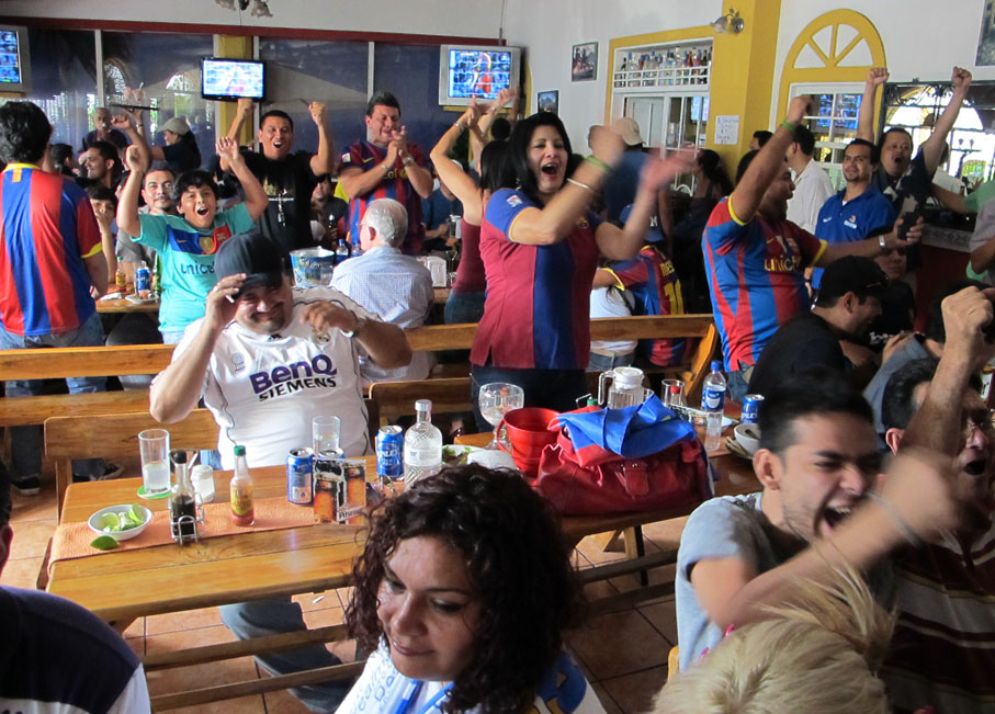 Aficionados salvadoreños reunidos en un bar disfrutan de un clásico del fútbol español. Foto de Francisco Campos.