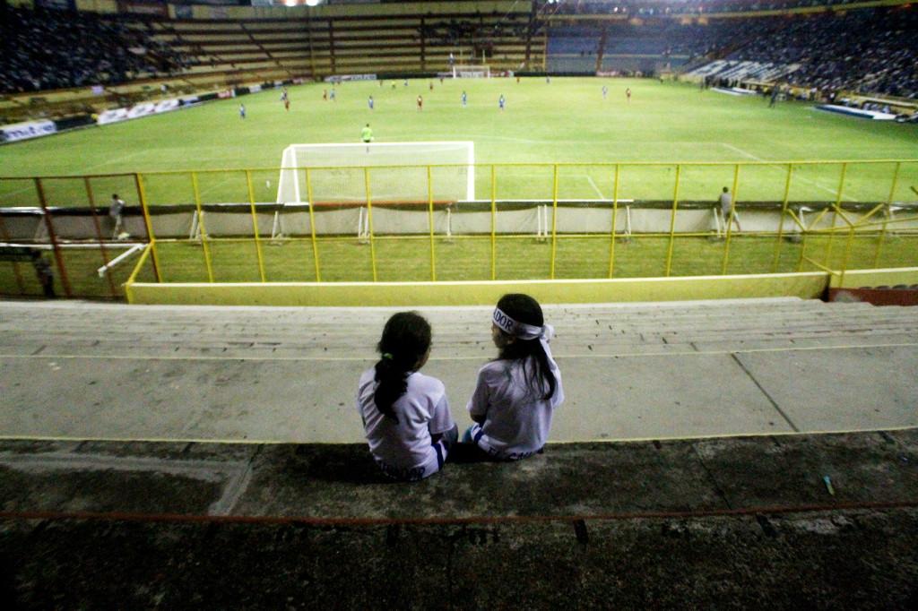 Dos niñas contemplan un juego de la selección salvadoreña de fútbol. Foto de Frederick Meza.
