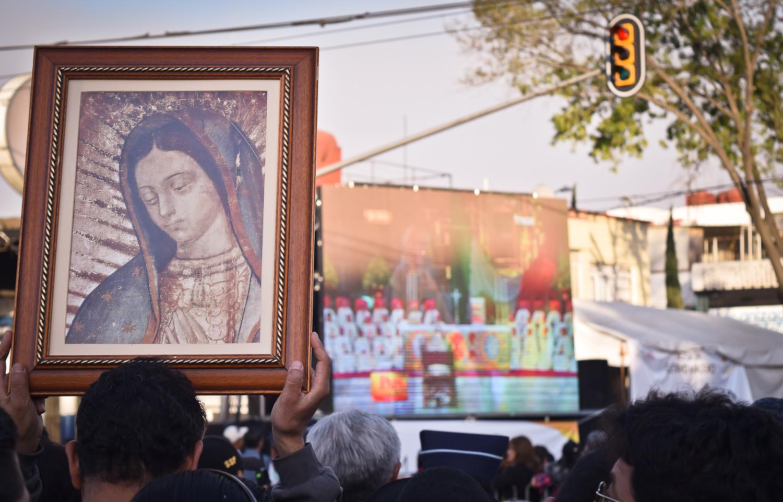 Un peregrino eleva un cuadro con la imagen de la Virgen de Guadalupe, mientras observa en pantalla gigante la transmisión de la misa que el papa Francisco ofrecería en la Basílica de Guadalupe. Foto/Orus Villacorta.