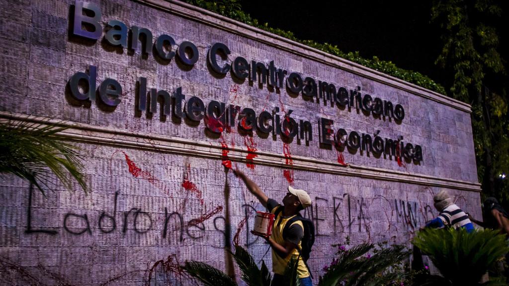Manifestantes universitarios parte de ''Los Indignados'' lanzan pintura en la fachada del Banco Centroamericano de Integración Económica (BCIE) en Tegucigalpa, Honduras, como parte de las protestas por el crimen de Berta Cáceres. Foto FACTUM/Salvador MELÉNDEZ.