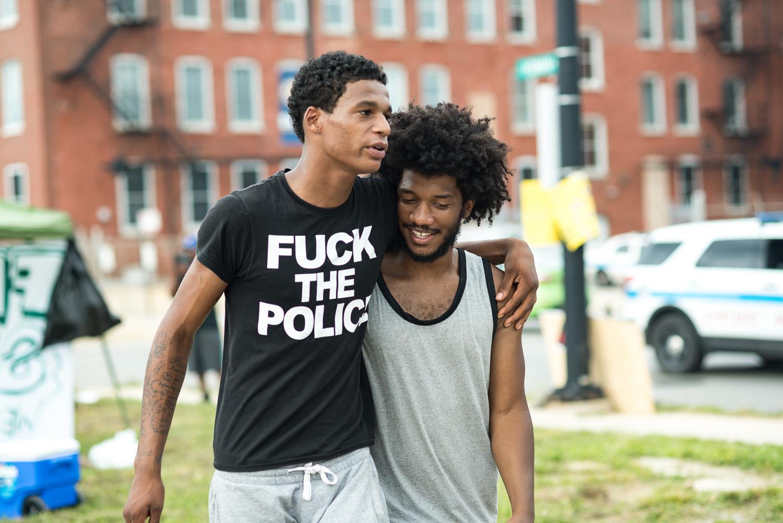 Dos activistas del campamento Freedom Square. La camiseta de uno de ellos demuestra las tensiones que las comunidades de afrodescendientes mantienen con la Policía. Foto cortesía de Sarah-Ji.