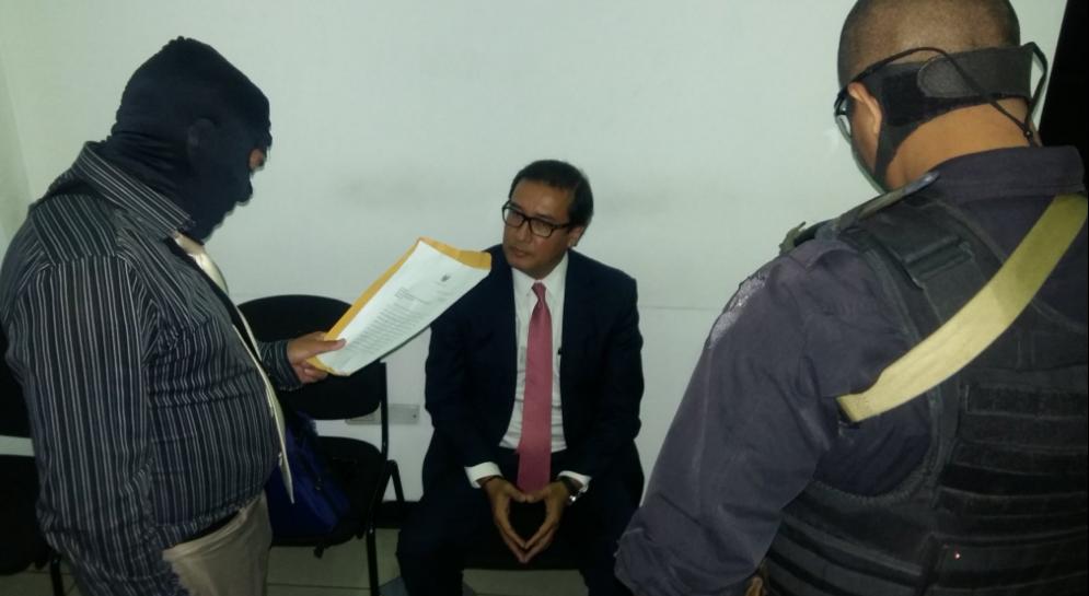 Un policía lee orden de captura contra el exfiscal general Luis Antonio Martínez. Foto: Fiscalía.