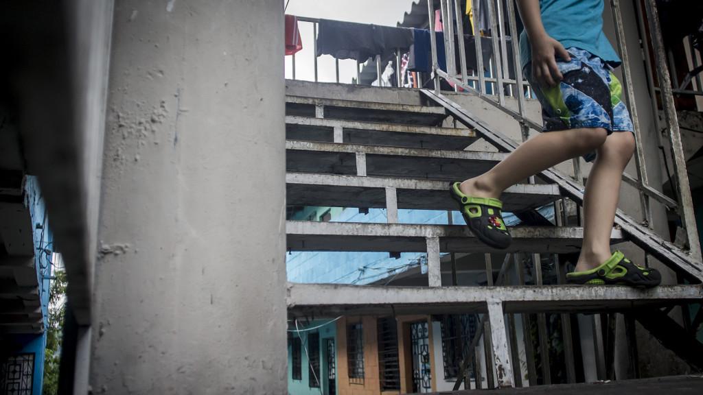 Un menor baja las gradas de la tercera planta de los Apartamentos América en San Salvador, para ir a visitar a un vecino que vive en el nivel de abajo. El sonido de las puertas al abrir y cerrarse es lo más audible en todo el día y a travez de las ventanas cerradas algunas voces de los habitantes que pasan la mayor parte del tiempo encerrados. Foto FACTUM/Salvador MELENDEZ