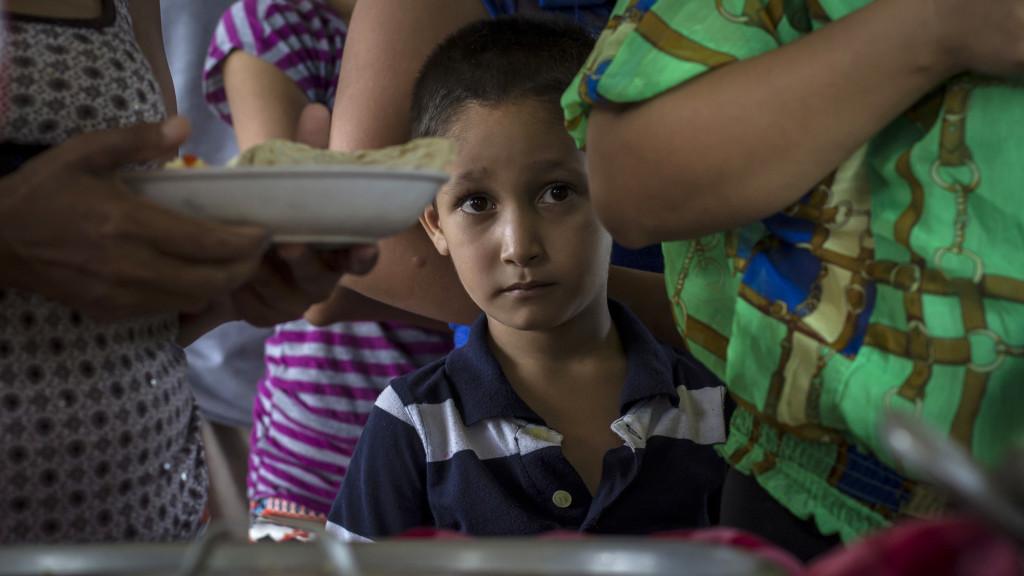 """El 16 de Septiembre de 2016 en el municipio de Caluco, en Sonsonate, la comuna instaló por primera vez después de terminada la guerra civil en El Salvador, lo que se dio por llamar """"el primer campo de refugiados en tiempos de paz"""" debido al exodo de varias familias del Cantón El Castaño que huyeron por que pandilleros de la Pandilla 18 Revolucionaria asesinaron a dos personas del lugar.En la imagen un menor espera turno para recibir su almuerzo. Foto FACTUM/Salvador MELENDEZ"""