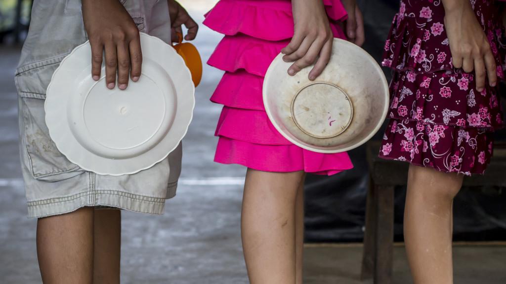 Los refugiados por la violencia por pandillas en Caluco, Sonsonate pasaron un mes en el albergue improvisado con bolsas plásticas y armazones de malla ciclón. En la imagen tres menores hacen la fila, con sus platos en mano, para poder recibir el almuerzo de ese día. Foto FACTUM/Salvador MELENDEZ