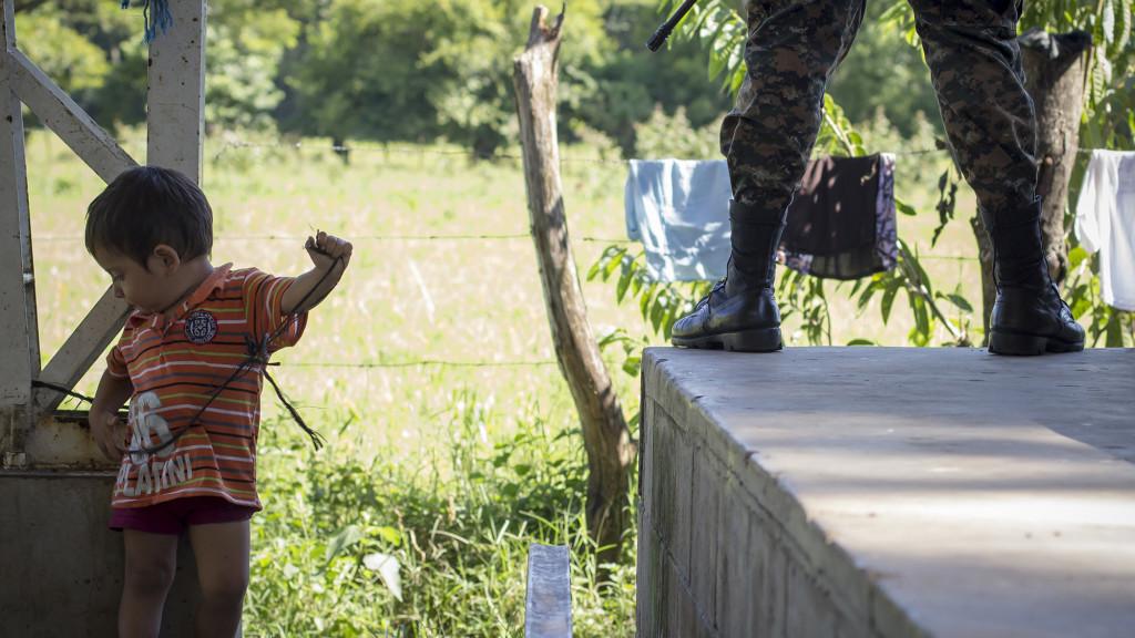 Un niño salvadoreño juega con un lazo en unas de las columnas metálicas que sostienen el techo de la cancha de baloncesto donde se instaló un albergue por la Alcaldía de Caluco, Sonsonate. El soldado a un lado, de unos 19 años de edad, vigilaba el perimetro. Foto FACTUM/Salvador MELENDEZ