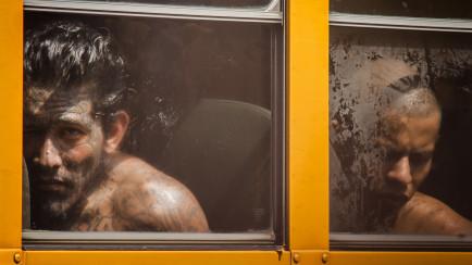 Un pandillero tatuado del rostro junto a otro esperaron en los autobuses un aproximado de cinco horas hasta que el último privado de libertad fuera evacuado del Penal de Cojutepeque. El Gobierno de El Salvador clausuró la prisión por no lograr controlar los ilicitos de los pandilleros dentro de las instalaciones. FOTO FACTUM/Salvador MELENDEZ