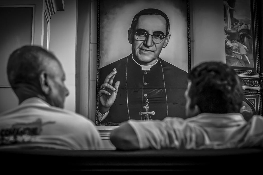 Dos salvadoreños conversan frente a la imagen oficial del Beato Oscar Arnulfo Romero, que ha sido colocada en unas de las columnas de la Catedral Metropolitana de San Salvador. Casi un año ha pasado de la Beatificación del Arzobispo Martir y los templos católicos ya han apartado lugar para la veneración del mismo.