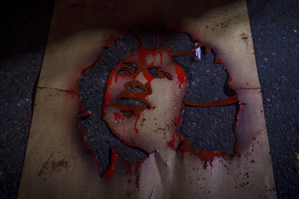 Una plantilla-icono del rostro de la asesinada Bertha Cáceres, utilizada por los manifestantes, permanece en el asfalto frente a la entrada del Banco Centroamericano de Integración Económica (BCIE) en Tegucigalpa, Honduras. Foto FACTUM/Salvador MELENDEZ