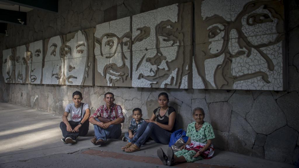 27 ANIVERSARIO DE LA CONMEMORACION DEL ASESINATO DE LOS SACERDOTES JESUITAS DE LA UCA. Peregrinos procedentes de Usulután, El Salvador, permanecen sentados al lado de uno mural con los rostros de los sacerdotes jesuitas y dos colaboradoras asesinadas por el ejercito salvadoreño en 1989. Este 16 de Noviembre se llegan a 27 años de la masacre durante la ofensiva guerrillera que puso fin a la guerra civil en El Salvador. Foto FACTUM/Salvador MELENDEZ