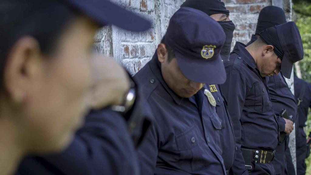 Agentes policiales permanecen cabisbajos en las afueras de la Iglesia Católica del caserío San Juan Los Planes, durante la misa de cuerpo presente del sub-inspector Lorenzo Rojas y su hijo, de 22 años, asesinados por pandilleros en la cima del volcán de San Salvador, jurisdicción de Quezaltepeque, La Libertad, el 18 de noviembre de 2016 Foto FACTUM/Salvador MELENDEZ