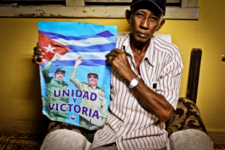 Manuel de Jesús Mejías, desmovilizado de las FAR, posa junto a una afiche de Fidel y Raúl Castro. Buena Vista, Playa, La Habana, Cuba. Foto de Nicola Chávez Courtright.