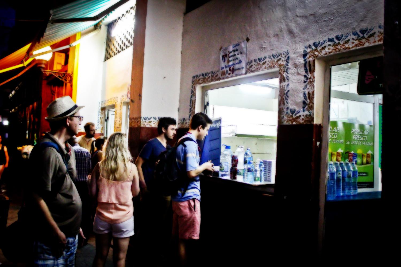 Turistas contemplan la oferta de bebidas carentes de alcohol en una tienda sobre la Calle Obispo. Habana Vieja, La Habana, Cuba. Foto de Nicola Chávez Courtright.