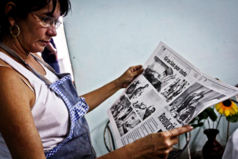 Gretel lee el periódico anunciando la muerte de Fidel Castro. Reparto Eléctrico, La Habana, Cuba. Foto de Nicola Chávez Courtright.