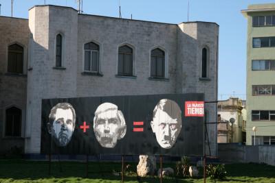 Valla instalada frente a la sección de intereses de Estados Unidos en La Habana en 2006, un año antes del décimo aniversario de los atentados dinamiteros. El rostro del centro es el de Posada Carriles. Foto de Sputnik, tomada de Flickr con licencia Creative Commons.