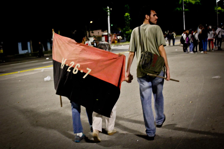 Tres generaciones caminan con la bandera del Movimiento 26 de Julio en el acto de masas. La Habana, Cuba. 29 de noviembre. Foto de Nicola Chávez Courtright.