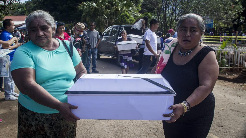 Dos mujeres salvadoreñas cargan una pequeña urna conteniendo las osamentas de una de las veintiún víctimas de la masacre de La Joya, en 1981. Foto FACTUM/Salvador MELENDEZ