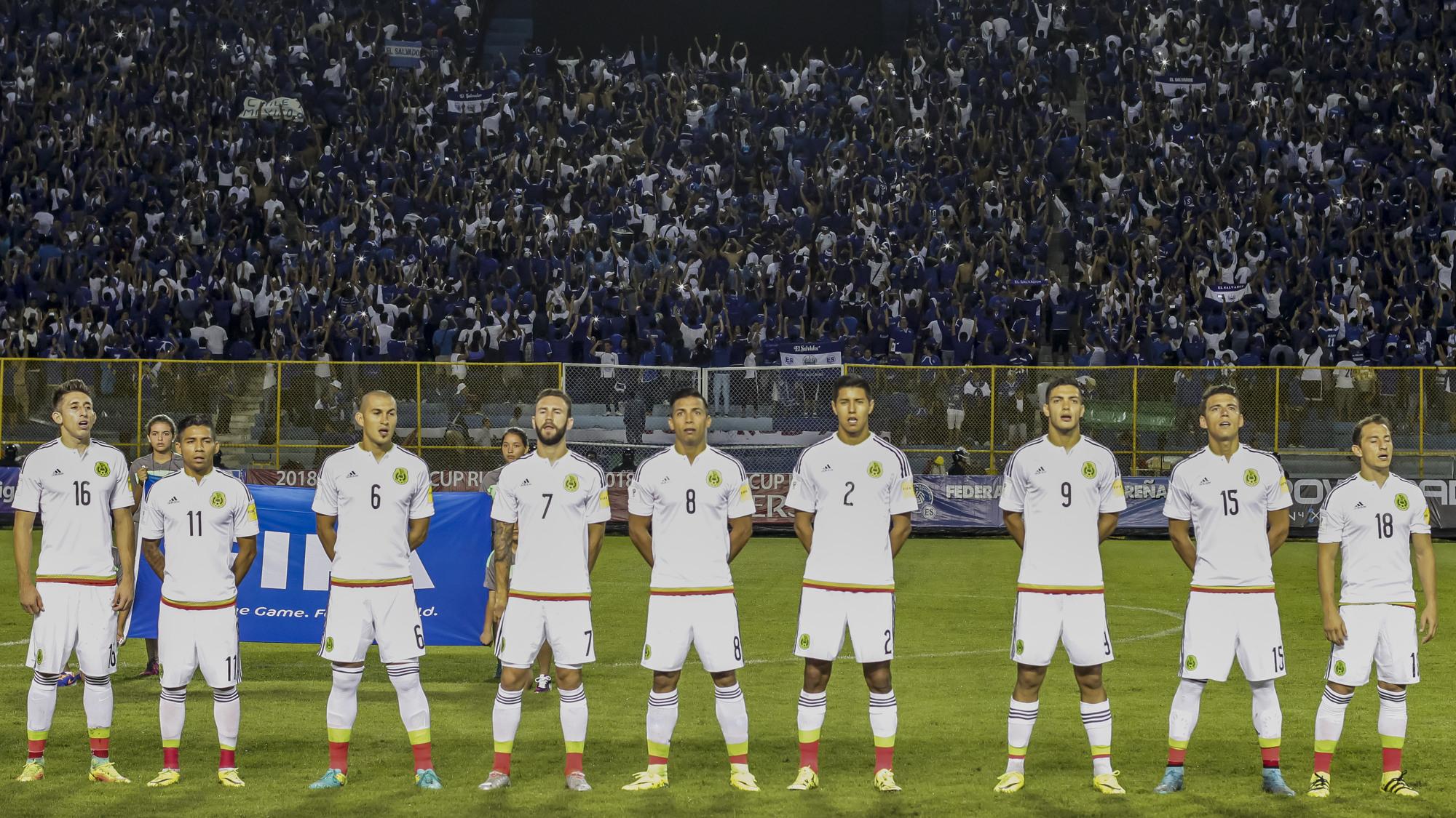 """Los seleccionados de México cantan su himno nacional en el engramillado del Estadio Cuscatlán, el 9 de septiembre de 2016, mientras la afición en """"el Vietnam"""" les da la espalda en forma de rechazo. Foto/Salvador MELENDEZ"""