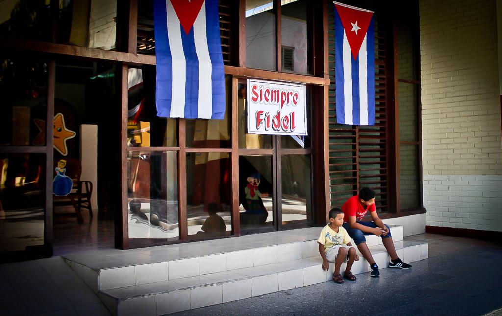 """Un padre cubano junto a su pequeño hijo permanecen sentados en la entrada de un establecimiento en La Habana, Cuba, con un rótulo de """"Siempre Fidel"""", haciendo alusión a la leyenda de su lider Fidel Castro, fallecido a los 90 años. Foto FACTUM/Nicola Chávez Courtright"""