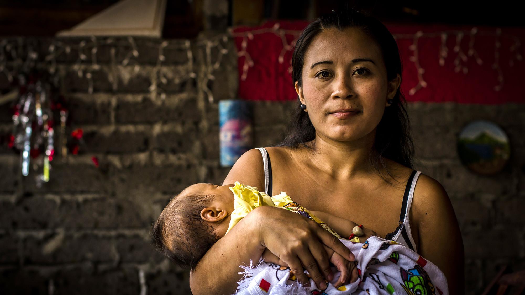 """Carmen Guadalupe Vásquez, de 26 años, sostiene a su hijo durante una entrevista con FACTUM en Cojutepeque, Cuscatlán. Guadalupe fue indultada por la Asamblea Legislativa por el delito de Homicidio Agravado, cuando sufrío un aborto espontáneo en el 2007. Gracias a la iniciativa del movimiento por las mujeres """"Las 17"""", Guadalupe ahora reconstruye su vida junto a su hijo. Foto FACTUM/Salvador MELENDEZ"""
