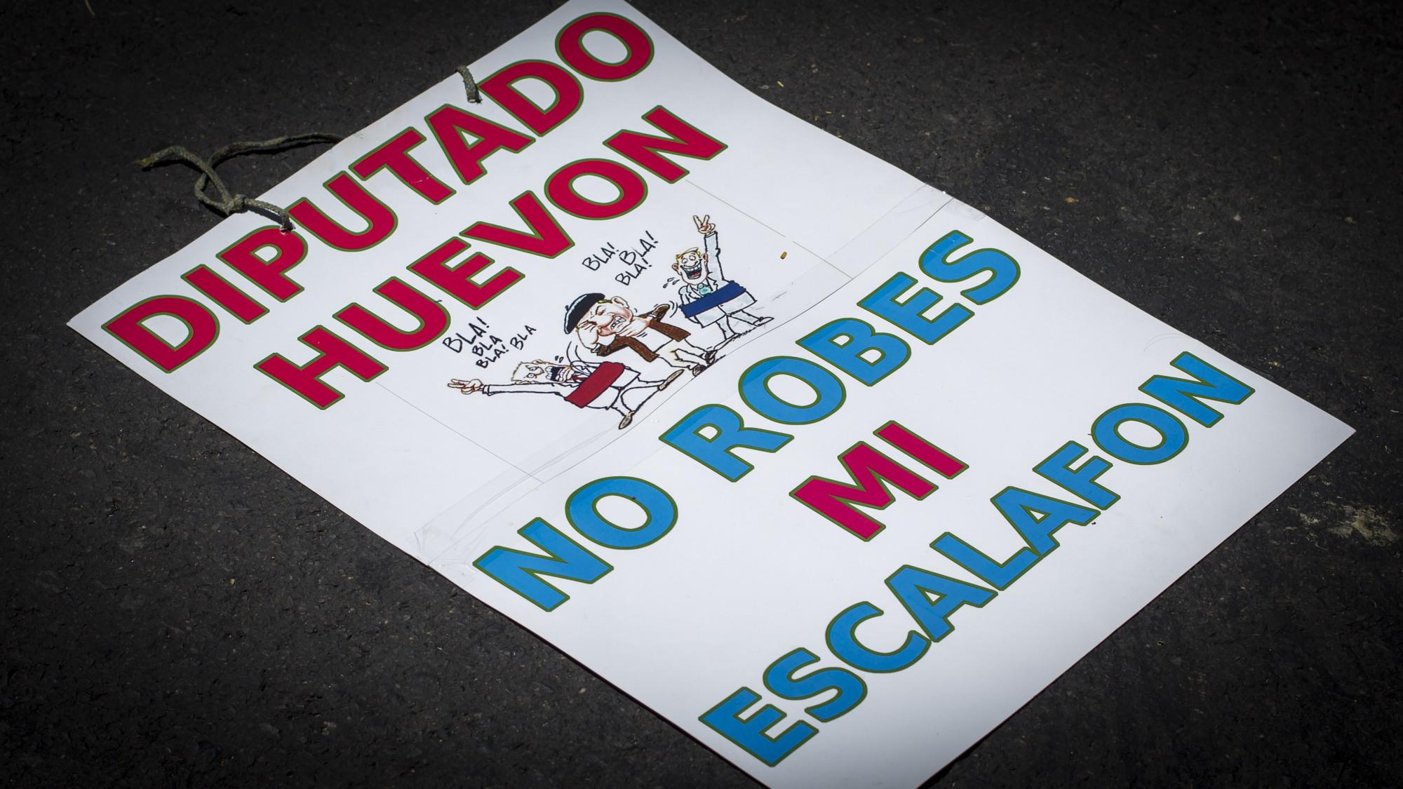 Una de las pancartas contra los diputados de la Asamblea Legislativa permanece en el asfalto en San Salvador, el 29 de Septiembre de 2016, como parte de las protestas en contra del gobierno que quiere anular una ley de salarios que les asegura aumentos cada año. Foto FACTUM/Salvador MELENDEZ